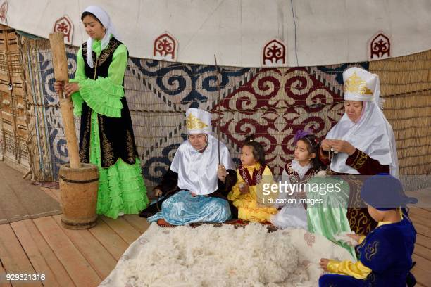 Family in traditional Kazakh clothes working wool into felt and yarn next to a yurt at Huns Village