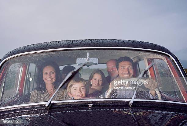 family in vintage car, smiling, portrait - groupe moyen de personnes photos et images de collection