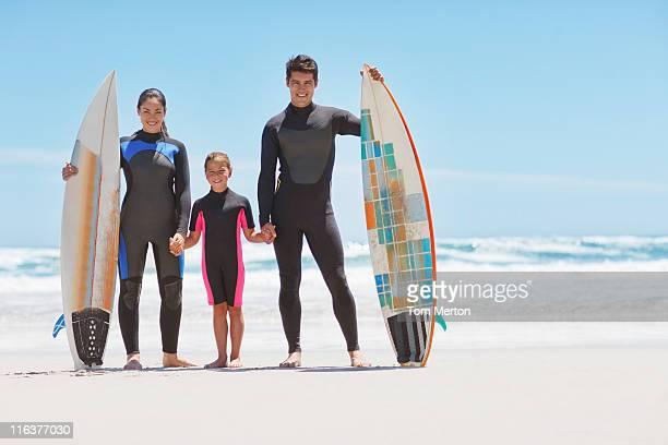 família em traje de mergulho com pranchas de surf na praia - traje de mergulho - fotografias e filmes do acervo