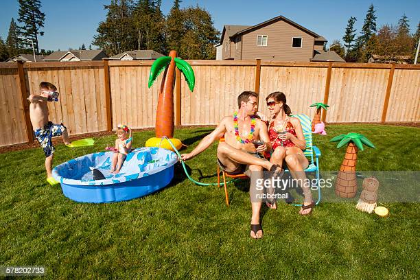 Family in yard with childrens pool and cocktails