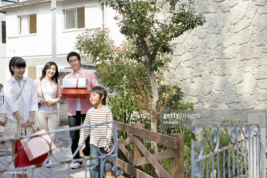 Family including boy and girl (6-13) getting back home with shopping : Stockfoto