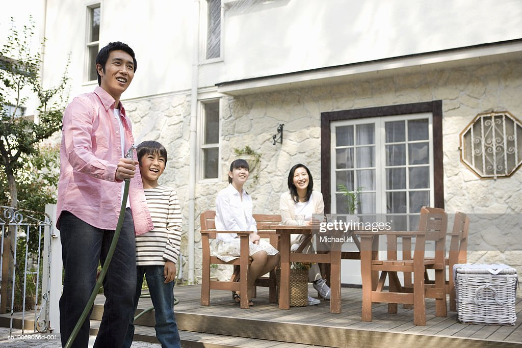 Family including boy and girl (6-13) relaxing outside house : Stockfoto