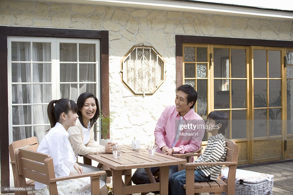 Family including boy and girl (6-13) sitting outside house : Stockfoto