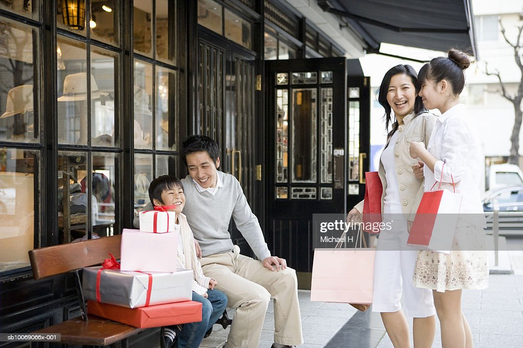 Family including boy and girl (6-13) sitting outside store : Stockfoto