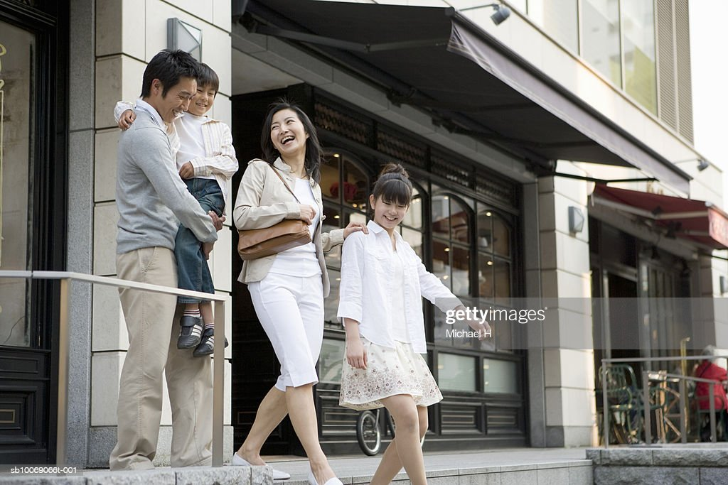 Family including boy and girl (6-13) walking out of store : Stockfoto
