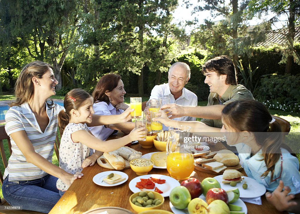 Family, including children (7-11) sitting at table in garden, toasting with orange juice and smiling : Stock Photo