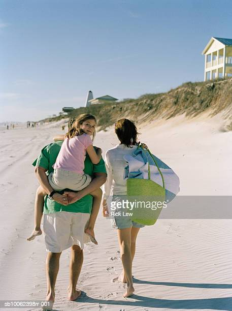 family including daughter (8-9 years) walking on beach, rear view - 30 39 years photos et images de collection