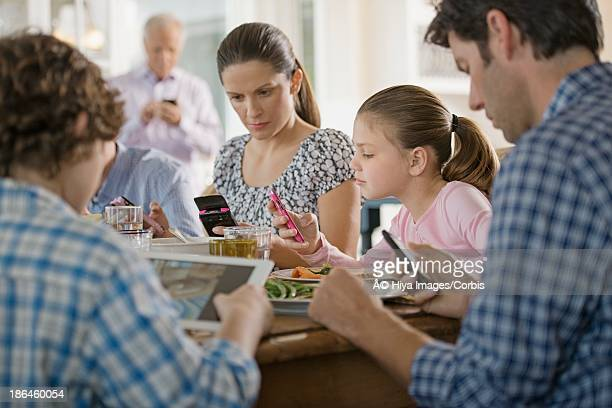 family including kids (8-9) texting at dinner table - addict stock photos and pictures