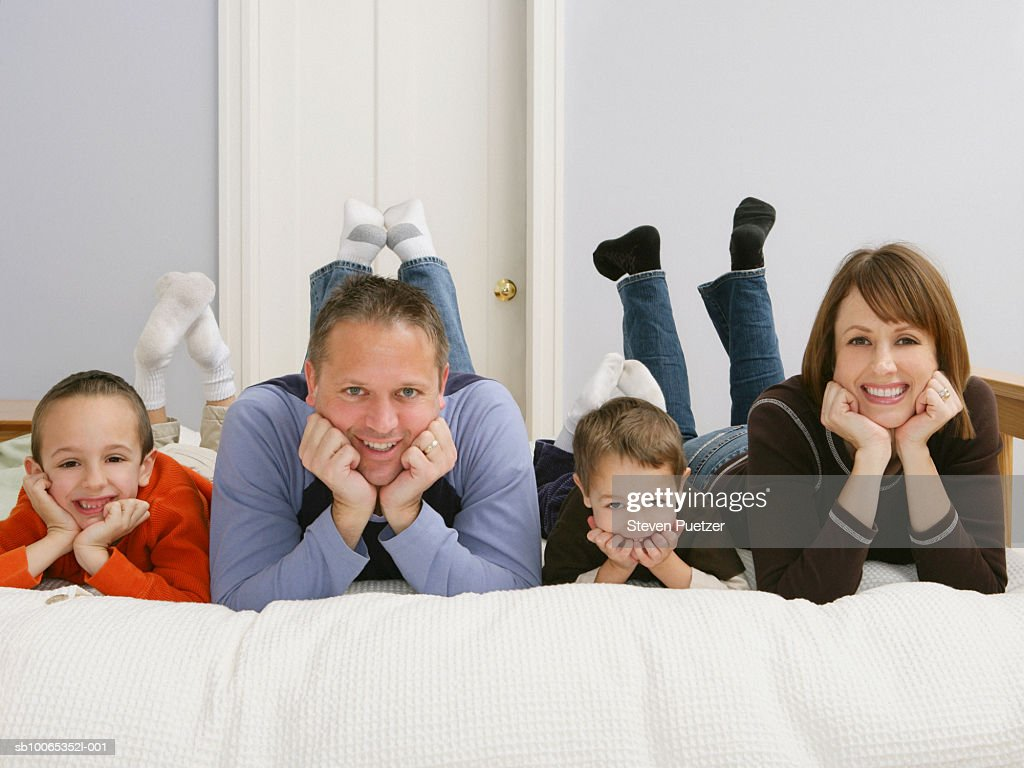 Family including two boys (5-7) lying on bed, smiling, portrait : Foto stock