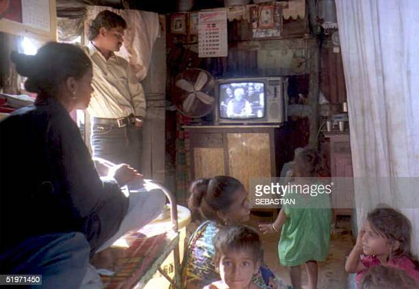 A family inside a hut in the Colab district of Bombay the broadcast 15 March of the Indian government's annual budget by Finance Minister Manmohan...