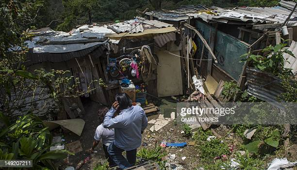A family inside their house made with carboard at the edge of a ravine in a poor zone of Mexico city on July 24 2012 AFP PHOTO/OMAR TORRES