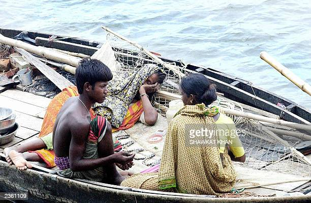 A family involved in the fishing industry take a rest in their boat on the river Meghna near Munsheganj 27 July 2003 At least 173 fishermen were...