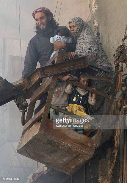 A family is evacuated with a crane from a damaged building following a reported airstrike on April 23 2016 in the rebelheld neighbourhood of Tareeq...
