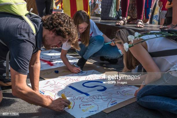 A family is pictured while preparing banners for the marathon for democracy day Pro independence sovereigntists have called a marathon for democracy...
