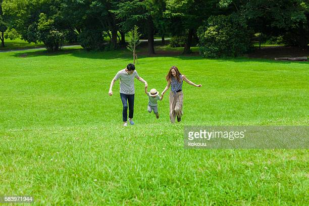 Family is running hand in hand in the park