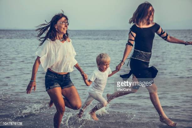 family is running on the beach
