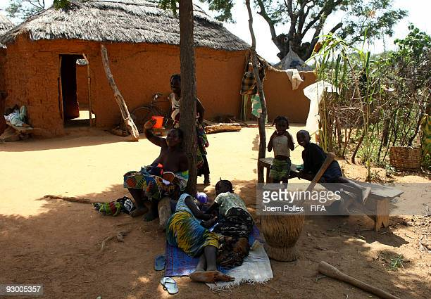 A family is seen in the shade next to their home on November 07 2009 in Bauchi Nigeria