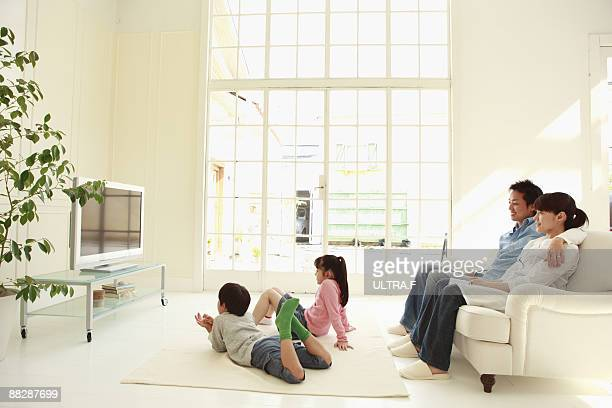 A family is sitting in front of a TV.