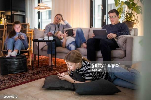 family is using technologies in living room at modern home - ausrüstung und geräte stock-fotos und bilder