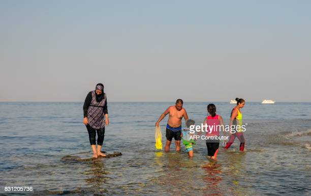 A family is walking in water in the Egyptian Red Sea resort of Sharm elSheikh on August 13 2017 / AFP PHOTO / MOHAMED ELSHAHED