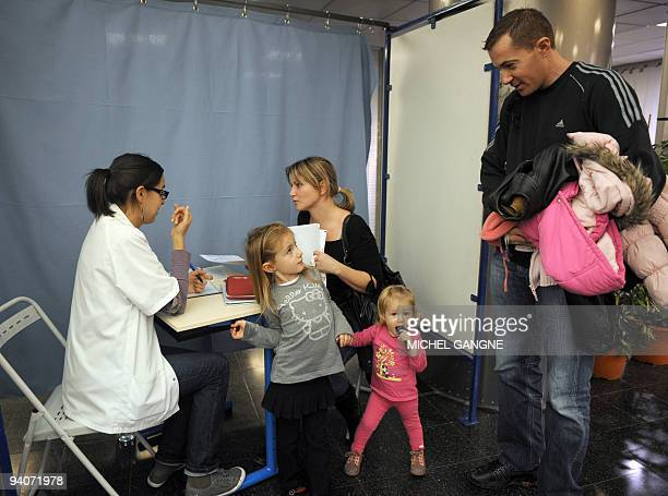 A family is welcomed before receiving a vaccination against the socalled swine flu on December 6 2009 in Marseille south of France as 185 vaccination...