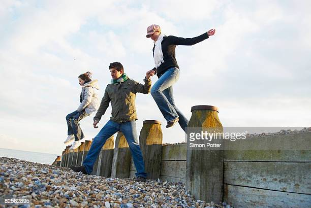 Family jump over breakwater on beach