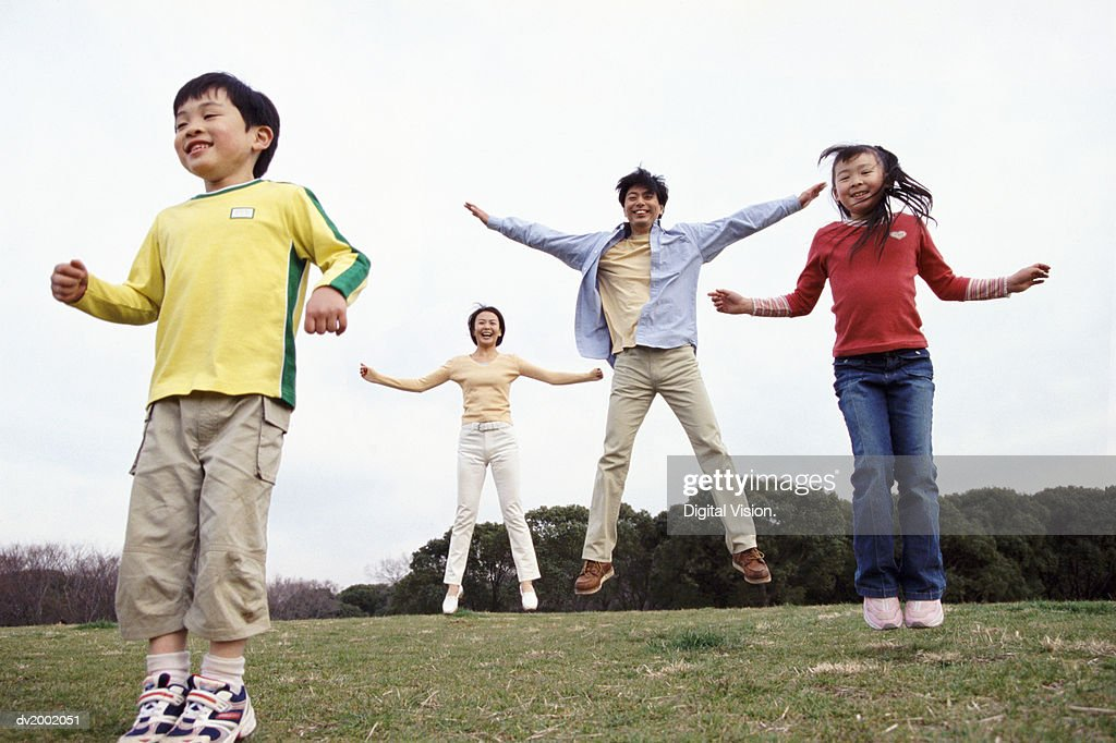 Family Jumping in a Park : Stock Photo