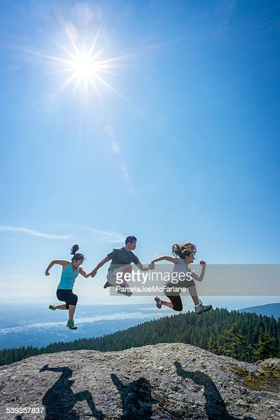 Family Jumping in Row on Mountain Top, Holding Hands
