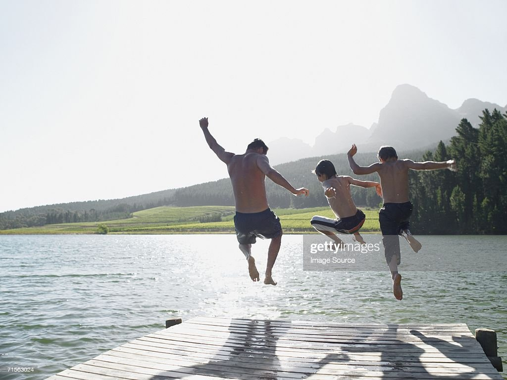 Family jumping into fijord : Stock Photo