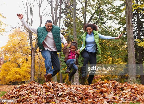 family jumping into pile of autumn leaves - girl mound stock pictures, royalty-free photos & images
