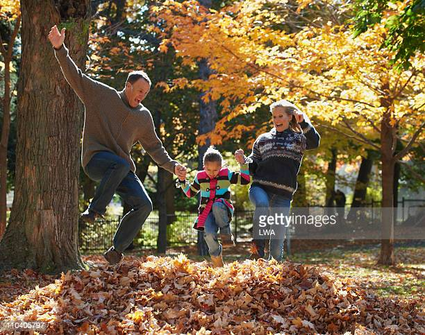 family jumping into pile of leaves - girl mound stock pictures, royalty-free photos & images