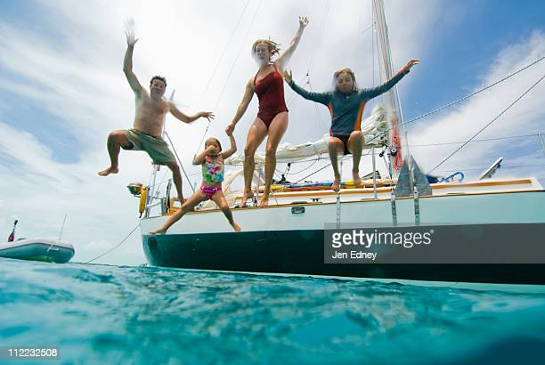 A family jumping off their boat