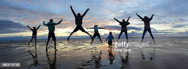 Family jumping on beach at sunset