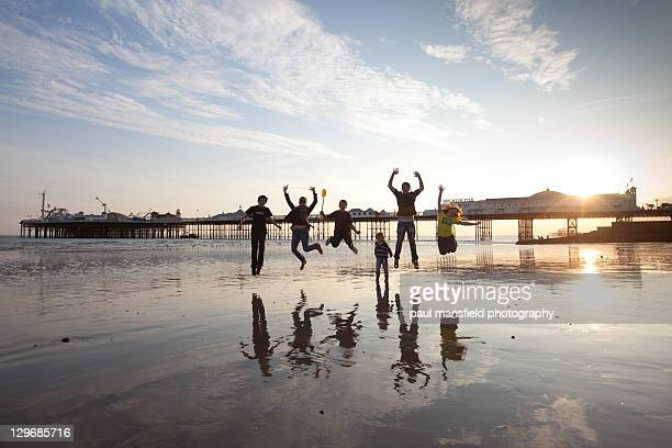 Family jumping on Brighton beach