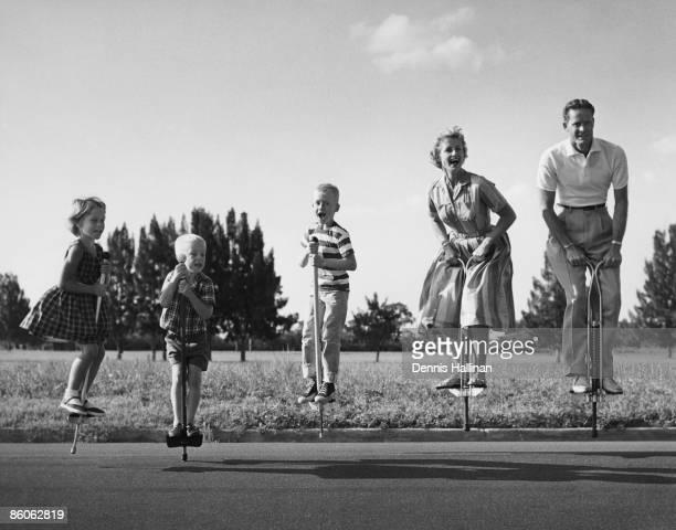 Family Jumping on Pogo Sticks