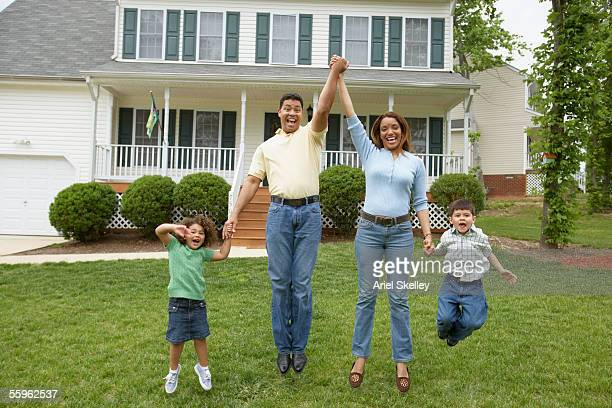 Family jumping together in front yard
