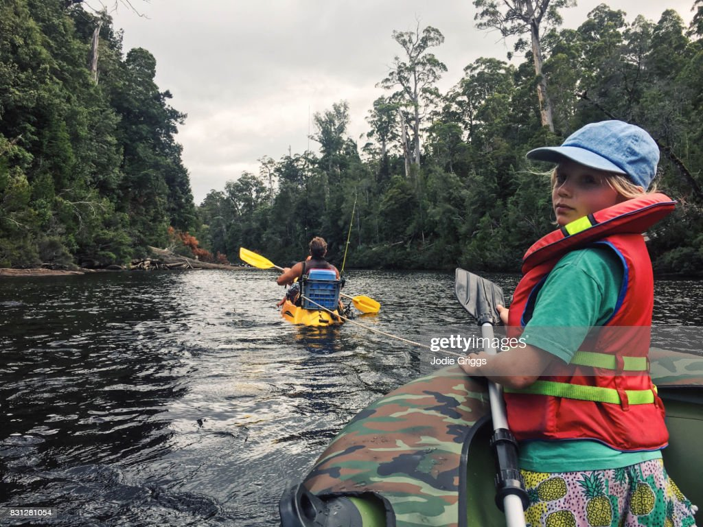 Family Kayaking And Rafting Down A River In The Wilderness Stock Photo