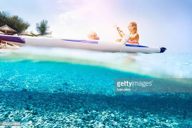 Family kayaking on beautiful beach