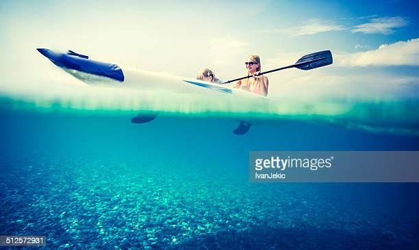 Família de caiaque no mar com Vista debaixo d'água
