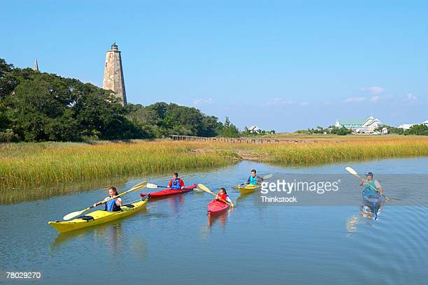 a family kayaks on marsh creek toward the viewer with a lighthouse in the background. - moeras stockfoto's en -beelden