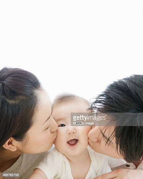 Family Kissing Their Child