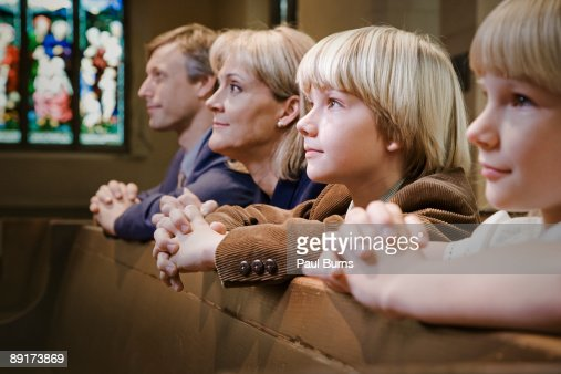 Family Kneeling And Praying In Church Stock Photo
