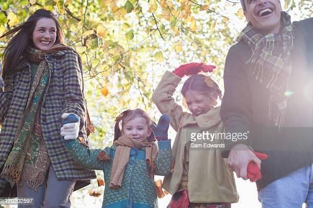 Família rir e de mãos dadas ao ar livre