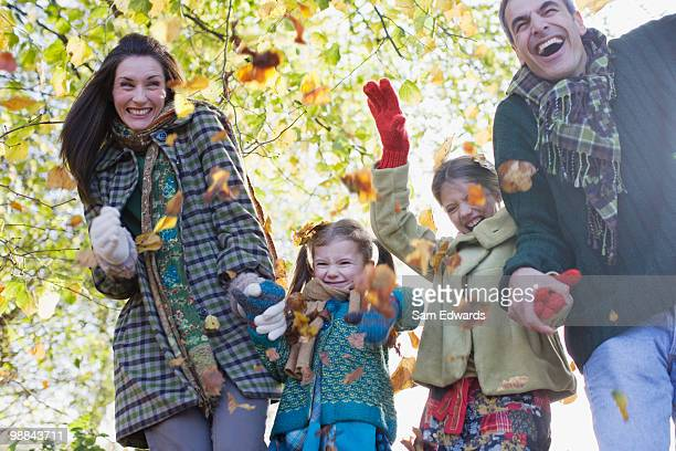 Family laughing and holding hands outdoors