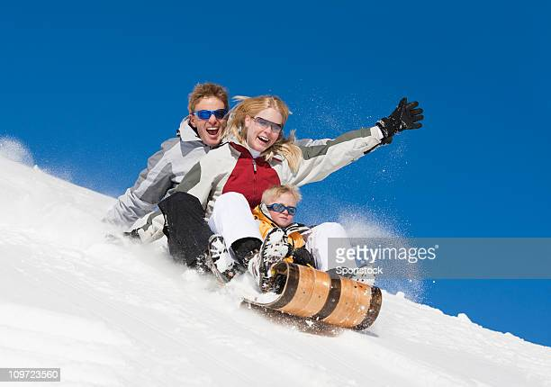 Family Laughing and Sledding Downhill