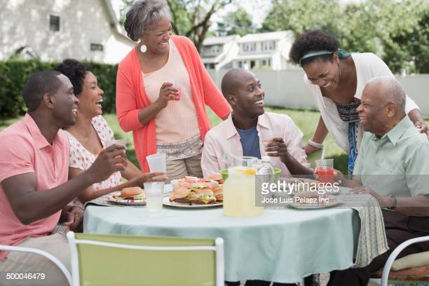 Family laughing at backyard barbecue