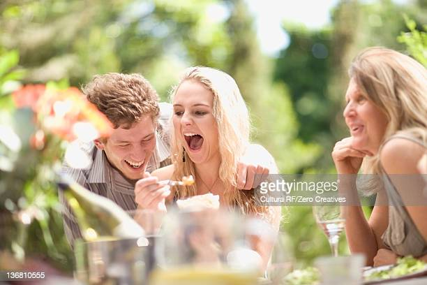 Family laughing at table outdoors