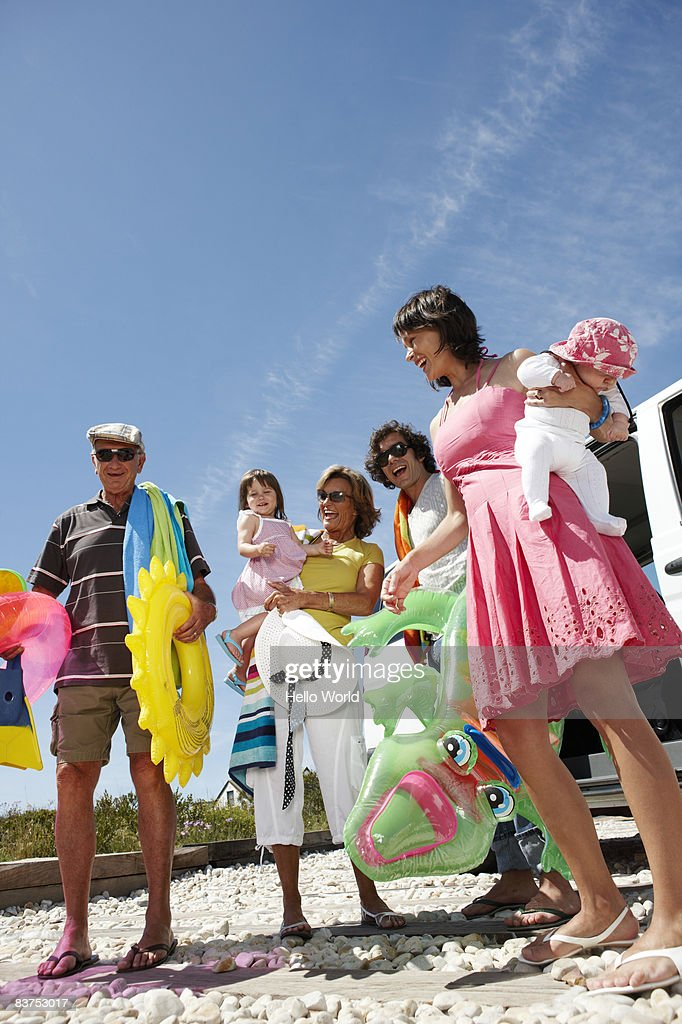 family laughing in front of car with beach toys : Stock Photo