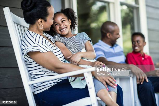 Family laughing on front porch