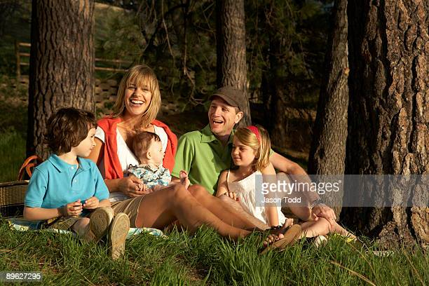 family laughing , sitting in grass - jason todd stock photos and pictures